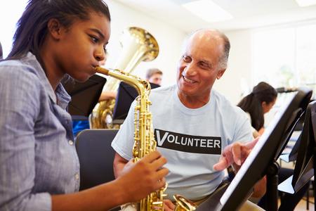saxofón: Chica aprender a tocar el saxofón en la Orquesta Escuela Secundaria Foto de archivo