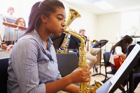Vrouwelijke Leerling Spelen Saxofoon In High School Orchestra Stockfoto