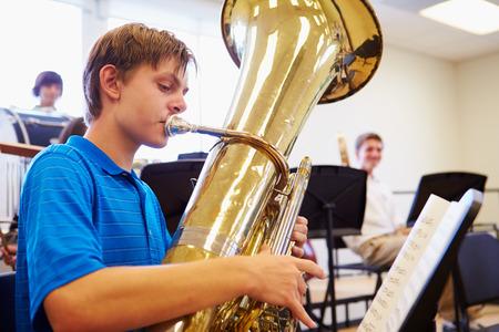 orquesta: Alumno Hombre que juega la tuba En Orquesta Escuela Secundaria