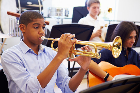 Male Pupil Playing Trumpet In High School Orchestra Stok Fotoğraf