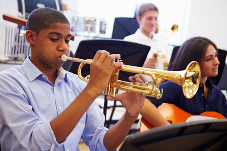 Male Pupil Playing Trumpet In High School Orchestra Foto de archivo