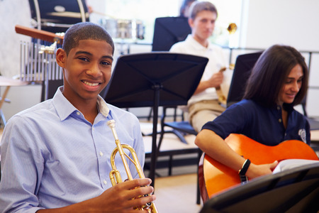 Male Pupil Playing Trumpet In High School Orchestra photo
