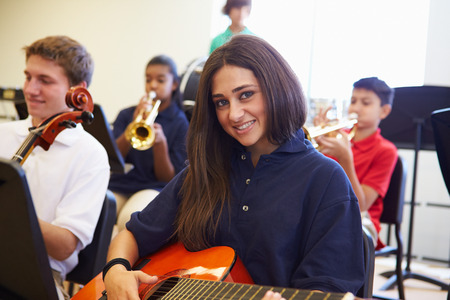 salon de clases: Alumno Mujer tocando la guitarra en la Orquesta Escuela Secundaria