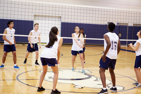 High School Volleyball Match In Gymnasium 免版税图像