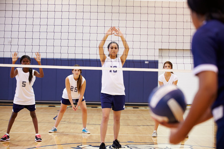 High School Volleyball Match In Gymnasium photo