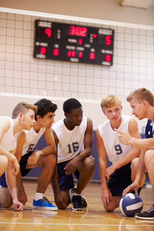 Male High School Volleyball Team Having Team Talk From Coach photo