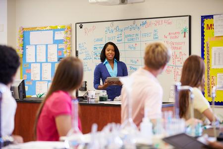 high school teacher: Teacher And Pupils In High School Science Class
