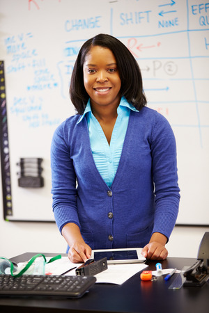 woman with camera: Science Teacher Standing At Whiteboard With Digital Tablet