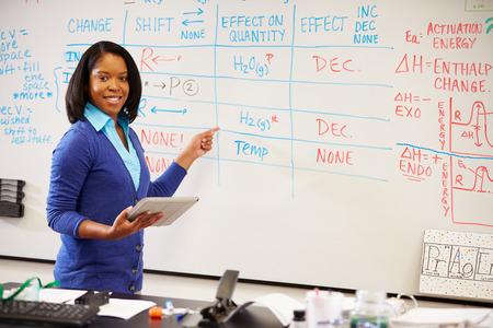 デジタル タブレットでホワイト ボードに立っている理科の先生 写真素材