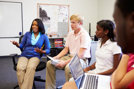high school teacher: High School Students Taking Part In Group Discussion Stock Photo