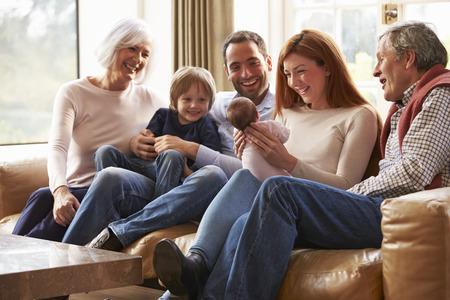 生まれたばかりの赤ちゃんをソファの上に座って多世代家族 写真素材