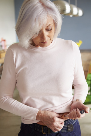 diabetes syringe: Senior Female Diabetic Injecting Themselves With Insulin