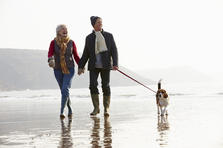 Senior Couple Walking Along Winter Beach With Pet Dog photo