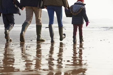 Close Up Of Family Walking Along Winter Beach photo