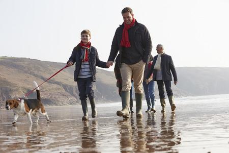 niños caminando: Multi generacional Recorre En La Playa invierno con el perro Foto de archivo
