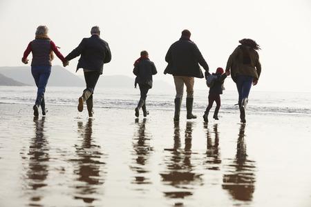 Multi Generation Family Walking On Winter Beach photo