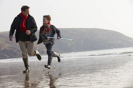 Father And Son Running On Winter Beach With Fishing Net photo