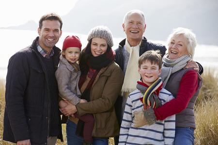 familias unidas: Multi generacional en dunas de arena en la playa del invierno Foto de archivo