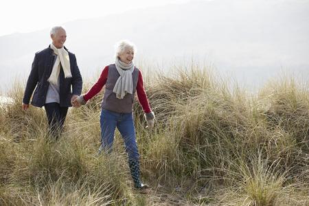 persona de la tercera edad: Pares mayores que recorren a trav�s de las dunas de arena en la playa del invierno