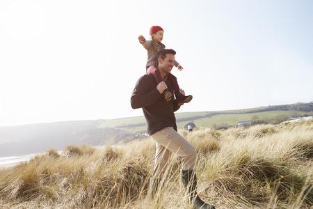 padre e hija: Padre e hija que recorren a través de las dunas en la playa del invierno