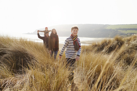 Family Walking Through Sand Dunes On Winter Beach Stock Photo