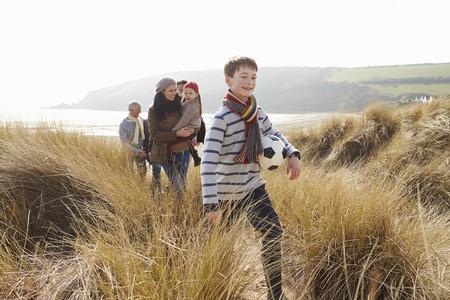 f�tes: Famille multi-g�n�rations dans les dunes de sable sur la plage d'hiver Banque d'images