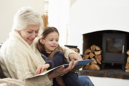 Grandmother And Granddaughter Reading Book At Home Together 스톡 콘텐츠