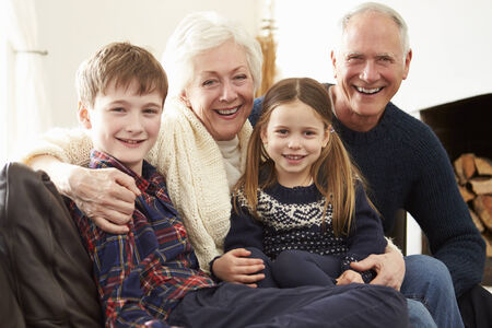 Portrait Of Grandparents Sitting On Sofa With Grandchildren photo