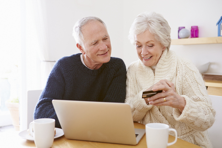 Senior Couple Using Laptop To Shop Online photo