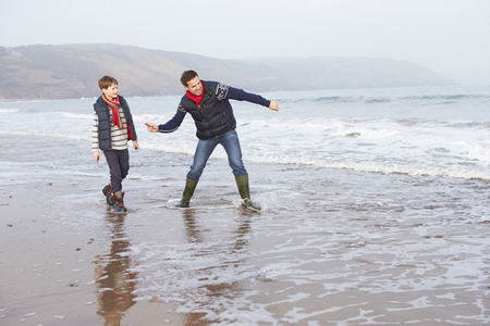 Father And Son Walking On Winter Beach And Throwing Stones photo