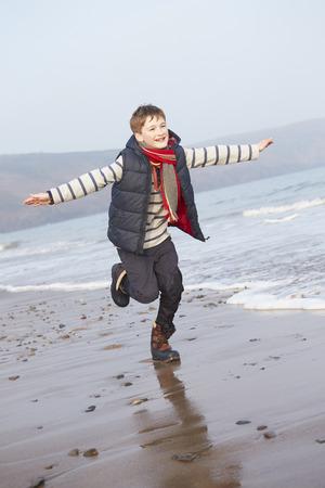 冬のビーチに沿って走る少年