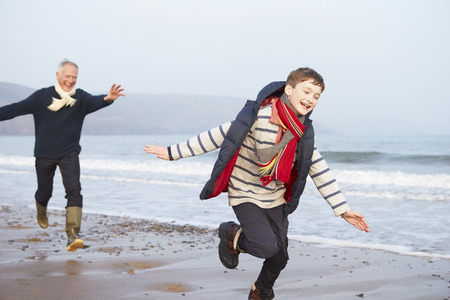 Grandfather And Grandson Running On Winter Beach photo