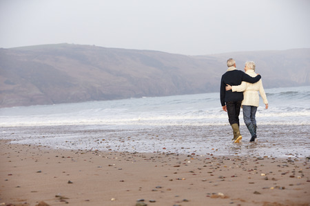 Senior Couple Walking Along Winter Beach photo
