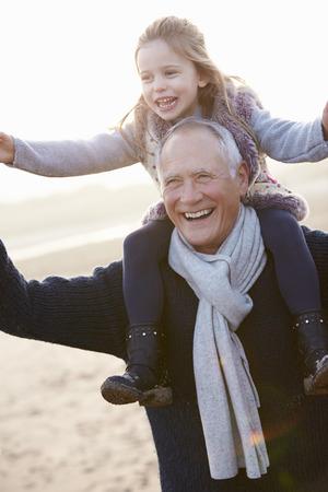 祖父と孫娘冬のビーチの上を歩いて 写真素材