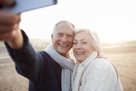 Senior paar staande op het strand nemen van Selfie