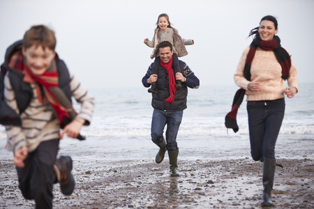 Family Running Along Winter Beach photo