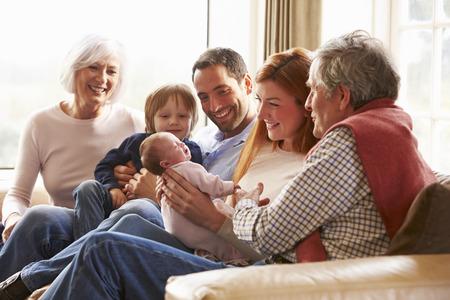 Família de várias gerações, sentado no sofá com bebê recém-nascido