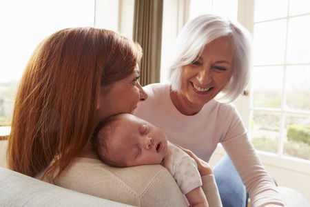 Mother And Grandmother With Sleeping Newborn Baby Daughter Standard-Bild