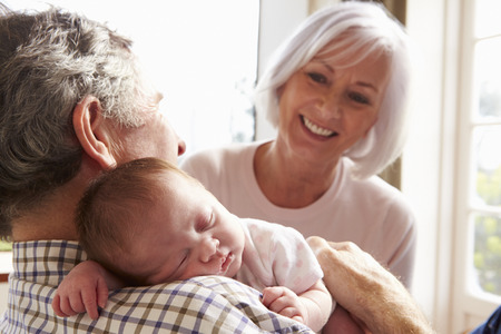Grandparents Holding Sleeping Newborn Baby Granddaughter photo
