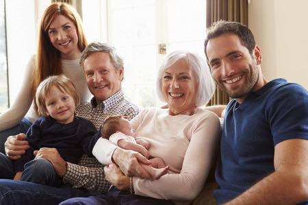 abuelos: Multi Generaci�n Familia que se sienta en el sof� con el beb� reci�n nacido