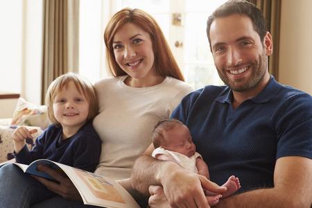 Family Sitting On Sofa With Newborn Baby photo