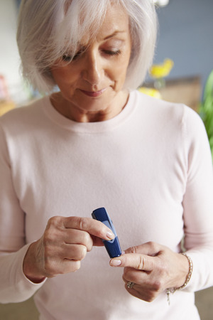 blood sugar: Senior Female Diabetic Checking Blood Sugar Levels Stock Photo