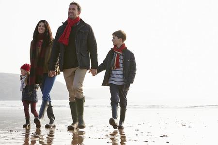 winter girl: Family Walking Along Winter Beach Stock Photo