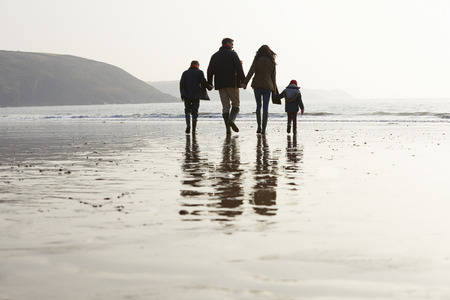 Rear View Of Family Walking Along Winter Beach