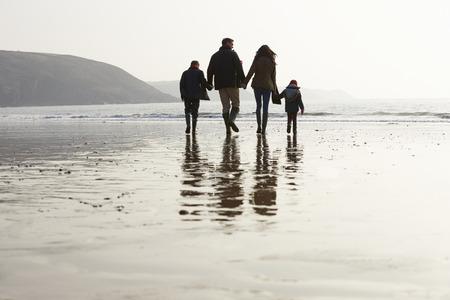 niños caminando: Vista posterior de la familia que recorre a lo largo de la playa de invierno