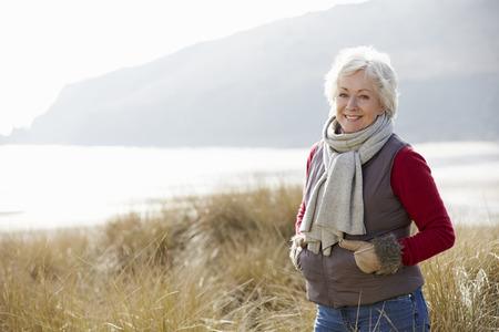 ancianos caminando: Mujer mayor que recorre a trav�s de las dunas de arena en la playa del invierno Foto de archivo