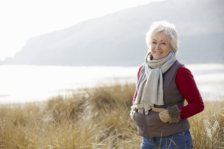 Senior Woman Walking Through Sand Dunes On Winter Beach