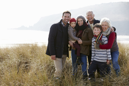 Multi Generation Family In Sand Dunes On Winter Beach Archivio Fotografico