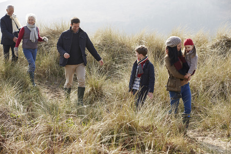 Multi Generation Family In Sand Dunes On Winter Beach Stock Photo