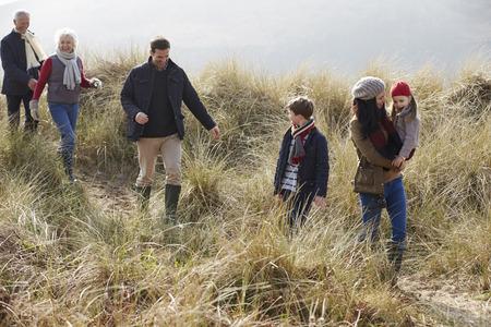 Multi Generation Family In Sand Dunes On Winter Beach Standard-Bild